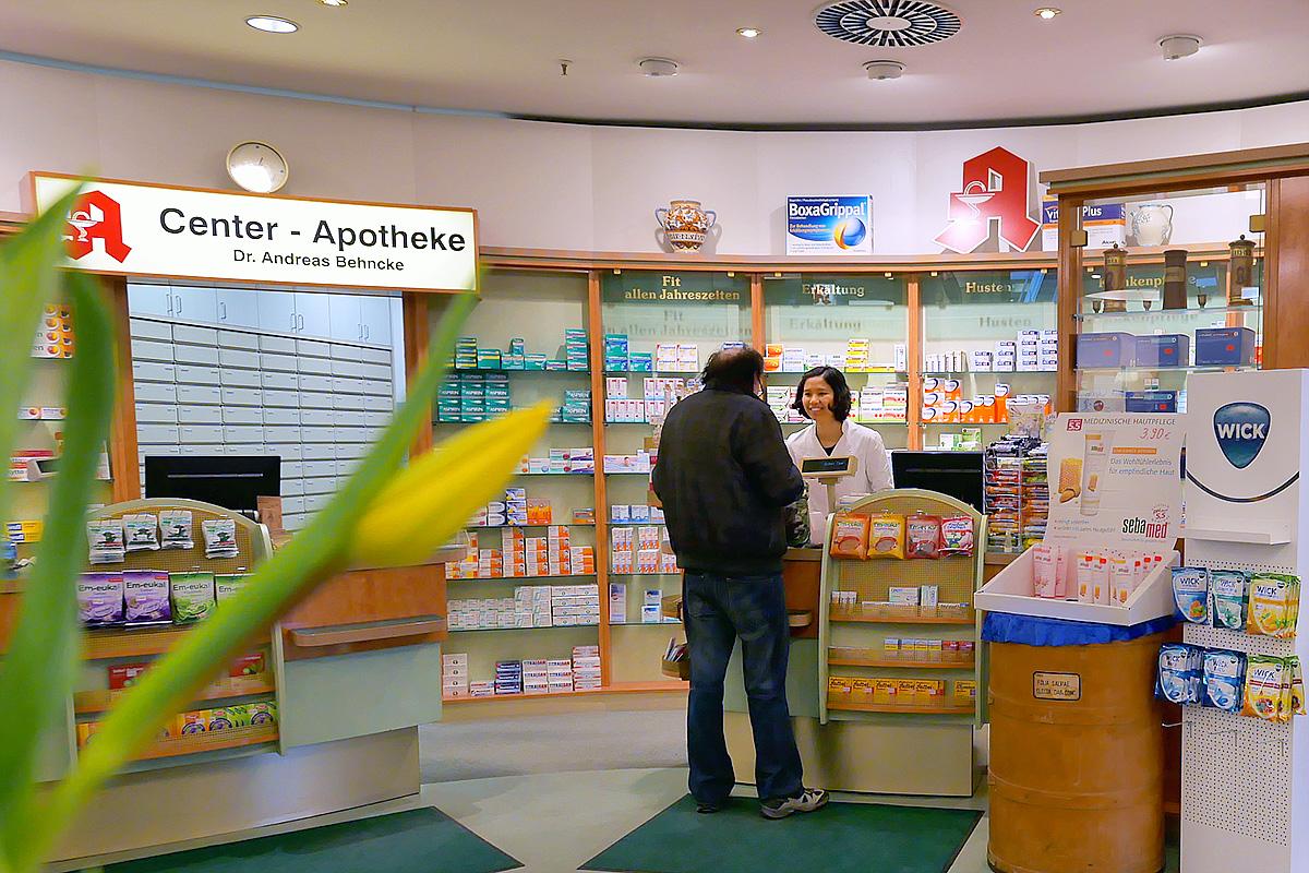 Eine Mitarbeiterin berät einen Kunden in der Apotheke Pankow